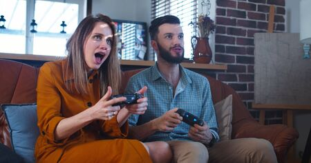 Young cheerful Caucasian couple have big fun playing videogames against each other at home on leisure time slow motion.