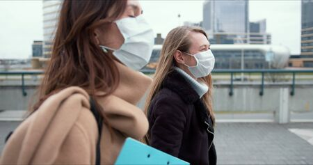 Epidemic control social workers. Two young Caucasian female doctors in face masks walk on city street during quarantine. Foto de archivo - 146125525