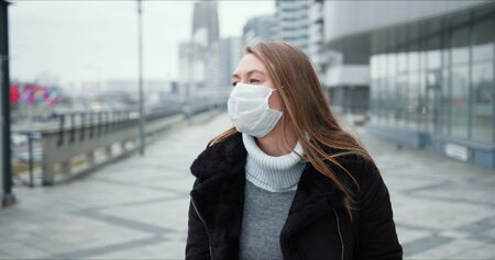COVID-19 epidemic protection. Young blonde woman in medical face mask walks along empty city street during lockdown.