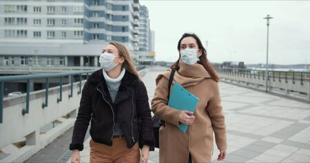 Two young doctor women wear masks walking in empty windy city street. Fear and danger atmosphere on epidemic quarantine.