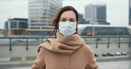 COVID-19 epidemic protection, danger and fear atmosphere. Portrait of beautiful Caucasian woman putting mask on outside.