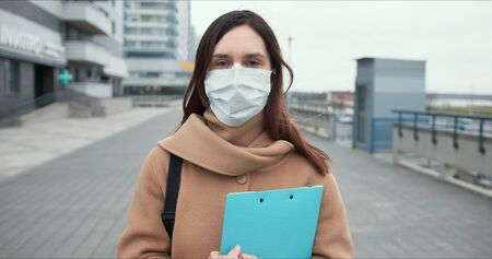 Epidemic control worker. Portrait of Caucasian social care woman in medical face mask in empty street during quarantine.