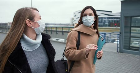 Social activism during coronavirus crisis. Two Caucasian female doctors walk on empty city street in medical face masks.
