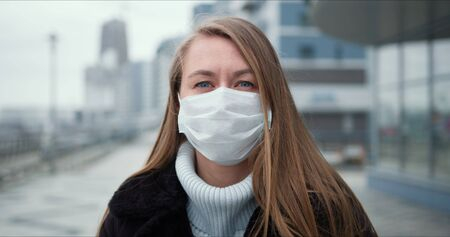 Epidemic quarantine. Portrait of young Caucasian woman wearing mask outdoors, turning head to camera in empty street.