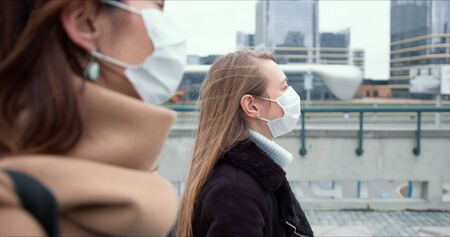 Epidemic control social workers. Two young Caucasian female doctors in face masks walk on city street during quarantine.
