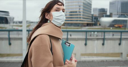 Coronavirus epidemic quarantine. Portrait of social care worker, young brunette woman in medical protection mask outside