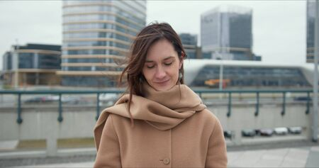 Portrait of beautiful happy healthy elegant business woman in beige coat looking at camera smiling in city background. Foto de archivo