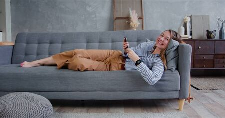 Self isolation concept. Young relaxed beautiful blonde woman scrolling feeds on smart phone, smiling at camera on sofa.