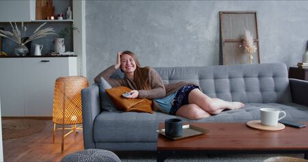 TV addiction on quarantine. Young happy attractive Caucasian blonde woman watching serial at home on comfortable sofa. Foto de archivo - 146125959