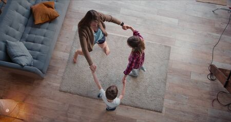 Top view young happy Caucasian mother dancing round dance with two cute teen kids, going crazy on vacation at home.