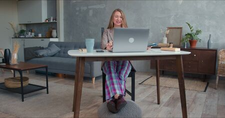 Comfortable work from home on lockdown. Young cheerful business woman in pajamas pants using laptop video conference app Foto de archivo