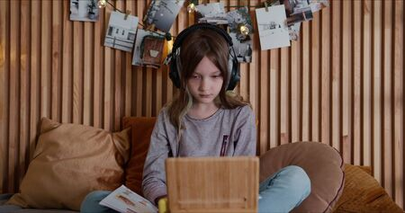 Young beautiful 8-10 year old Caucasian teenage girl studies alone at home using headphones and tablet on self isolation