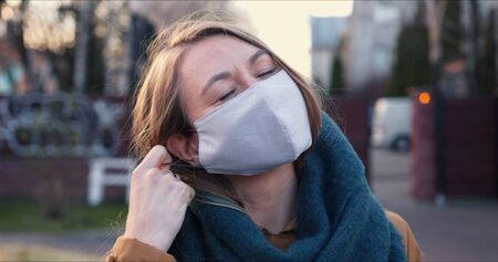 Lockdown ending. Portrait of young happy blonde woman taking protection mask off smiling outdoors on COVID-19 quarantine Foto de archivo - 146125764