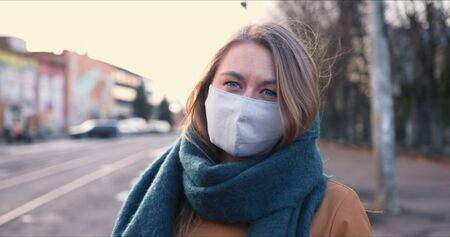 Epidemic control. Portrait of young blonde Caucasian woman wearing safety mask on face outdoors on COVID-19 quarantine. Foto de archivo