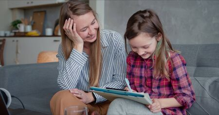 Happy attractive young Caucasian mother helping cute cheerful teenage daughter study and learn on quarantine at home.