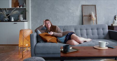 TV addiction on quarantine. Young happy attractive Caucasian blonde woman watching serial at home on comfortable sofa.