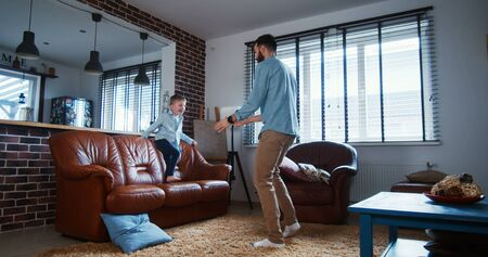 Happy young Caucasian father lifting his little son high, playing and having fun in modern light living room slow motion. Togetherness and love, child sharing exciting bonding time with dad at home.