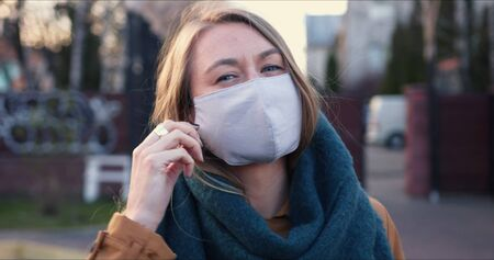 Lockdown ending. Portrait of young happy blonde woman taking protection mask off smiling outdoors on COVID-19 quarantine