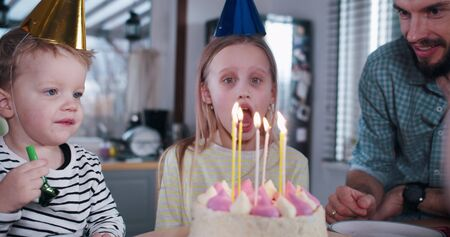 Happy young European teenage girl child blowing on birthday cake, celebrating party at home with family slow motion.