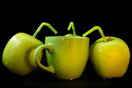 Green apples around a mug of Apple juice
