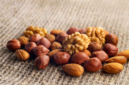 Hazelnuts, walnuts, and almonds lie on a factory-made sackcloth. Nuts are a high-calorie and healthy product.