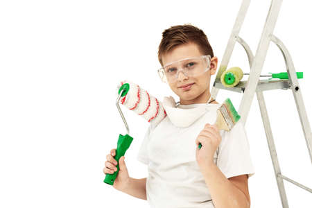 A boy with painting tools on a white background. Construction tools. Roller and stepladder. A little boy makes repairs