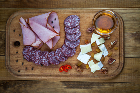 Kiev, Ukraine - February 26, 2018: Meat and cheese delicacies with honey, pepper and nuts on a wooden board. 写真素材