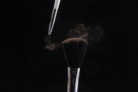 Kiev, Ukraine - February 26, 2018: Two brushes dispelled cosmetic powder on a black background. 報道画像