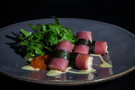 Kiev, Ukraine - February 26, 2018: Rocket salad with tuna, caviar and cheese sauce, on the black background, cooked in the restaurant