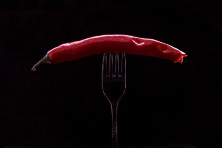Kiev, Ukraine - February 26, 2018: Snacked hot pepper, pinned on a fork on a black background.
