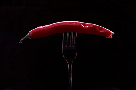 Kiev, Ukraine - February 26, 2018: Snacked hot pepper, pinned on a fork on a black background.