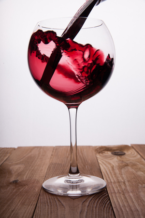 Kiev, Ukraine - February 26, 2018: Fusing red wine in a glass, on a wooden table and on a white background. 写真素材
