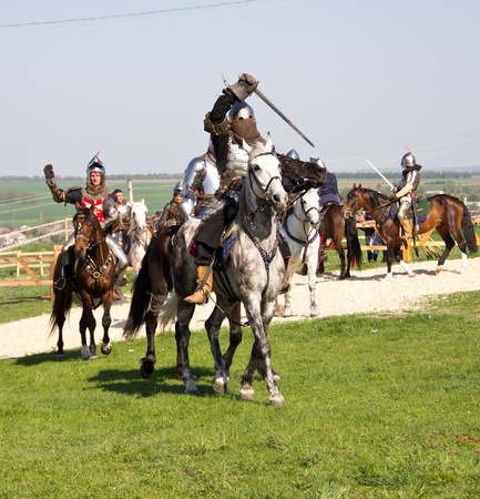 KHOTYN - APRIL 30: Group of  knights in armor fighting with swords on horseback - Medieval Khotyn Festival. April 30, 2012. Ukraine
