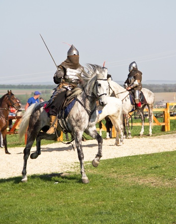 Knight in armor with sword riding on horseback photo