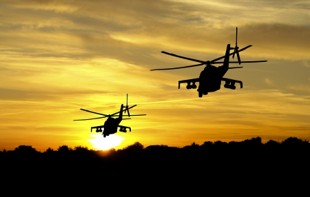 air war: Flying helicopter silhouettes on sunset background