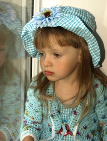 petite fille triste: Réfléchie petite fille regardant à travers la fenêtre Portrait