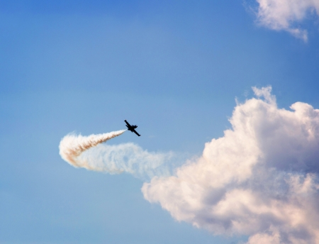 acrobatic: Aircraft with smoke trail flying on blue cloudy sky background