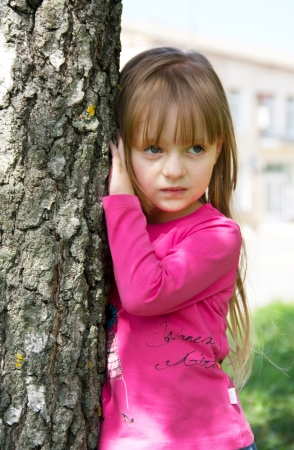 Little girl posing near birch tree  Close up photo