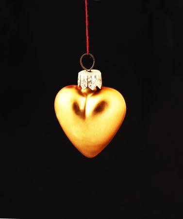 Hanging Christmas yellow heart  isolated on black background photo