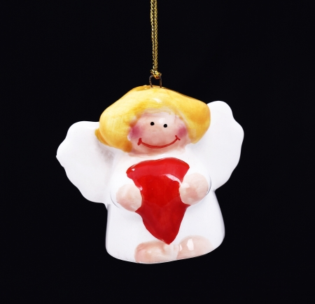 Cute Christmas angel with red heart hanging against black background photo