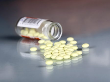 Pile of yellow tablets and bottle