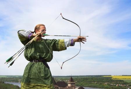 castillo medieval: Joven arquero con arco y flechas en traje medieval con el objetivo