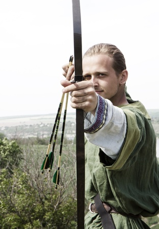 archer: Attractive young archer with bow and arrows in medieval costume aiming