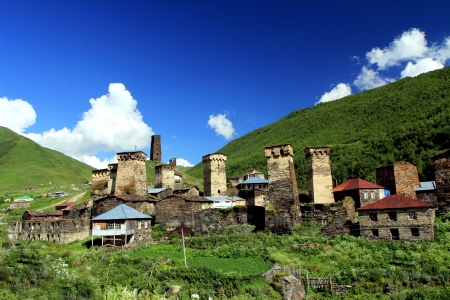 svaneti: Mountain village with ancient towers on blue cloudy sky background  Stock Photo