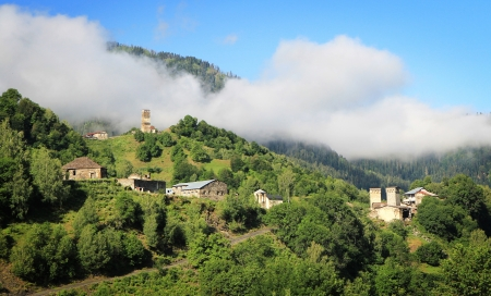 Mountain village with ancient towers in morning fog Stock Photo - 21049090