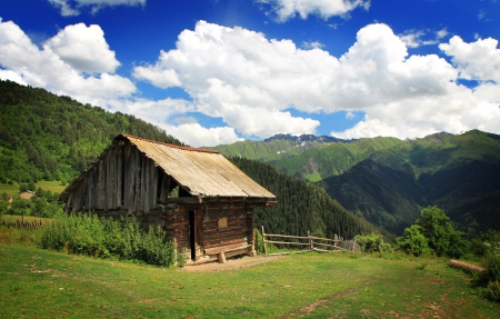 clody sky: Wooden house in mountains on blue clody sky background Stock Photo