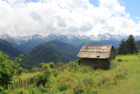 clody: Wooden house in mountains on blue clody sky background Stock Photo