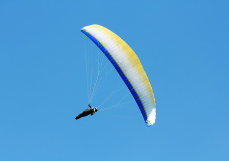 mosca: Paraglider flying on clear blue sky background