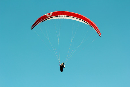 parachuting: Paraglider flying on clear blue sky background