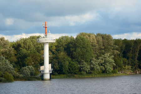 Navigational tower on the water for ships in summer weather.